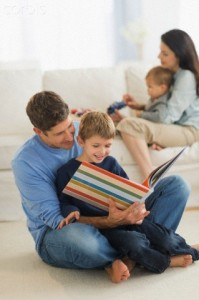 Parents with kids (12-17 months, 6-7) at home, father reading to son