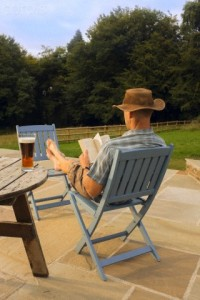 A Man Relaxing With a Book and Glass of Beer