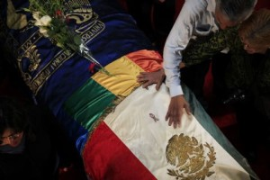The body of Mexican writer Monsivais lies in a coffin as people mourn during his wake in Mexico City
