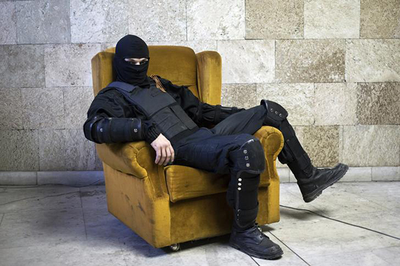 A masked pro-Russian protester sits on a chair as he poses for a picture inside a regional government building in Donetsk, eastern Ukraine. Photo by Marko Djurica