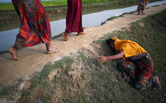 An exhausted Rohingya refugee cries for help to other refugees as they continue their way after crossing from Myanmar into Palang Khali, near Cox's Bazar, Bangladesh. Photo by Hannah McKay