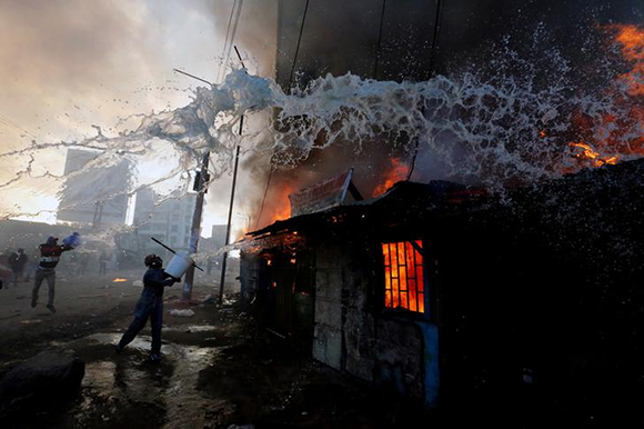 People try to put out a fire at properties set ablaze by rioters in Kawangware slums in Nairobi, Kenya. Photo by Thomas Mukoya
