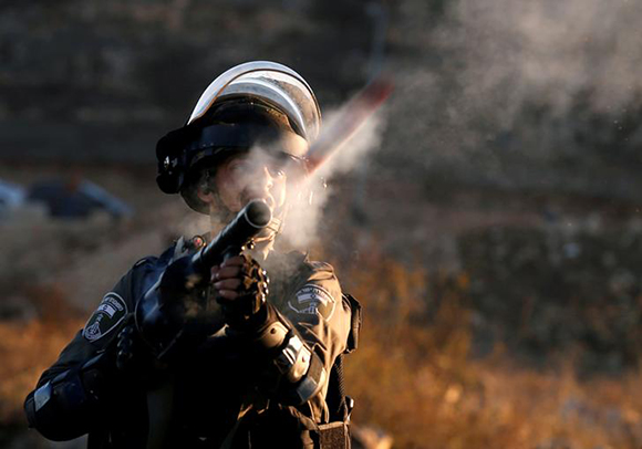 "An Israeli border policeman reacts as he fires towards Palestinian protesters during clashes as Palestinians call for a ""day of rage"" in response to U.S. President Donald Trump's recognition of Jerusalem as Israel's capital, near the Jewish settlement of Beit El, near the West Bank city of Ramallah December 8, 2017. Photo by Mohamad Torokman"