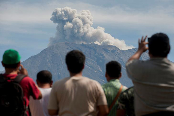 People watch as Mount Agung spews ash and smoke during an eruption from an obeservation post in Rendang, Karangasem, Bali, Indonesia December 9, 2017 Photo by Antara Foto