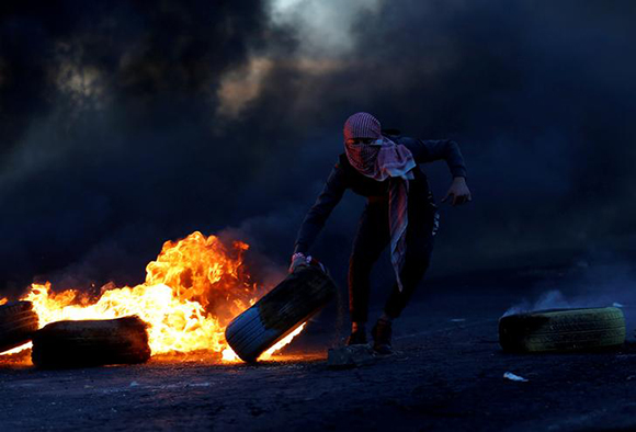 Palestinian moves a tire during clashes with Israeli troops at a protest against U.S. President Donald Trump's decision to recognize Jerusalem as Israel's capital, near the Jewish settlement of Beit El, near the West Bank city of Ramallah December 9, 2017. Photo by Mohamad Torokman