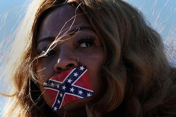 Edelia Carthan stands in silent protest with a confederate flag sticker covering her mouth during the official opening ceremony for the Mississippi Civil Rights Museum in Jackson, Mississippi, U.S., December 9, 2017. Photo by Carlo Allegri
