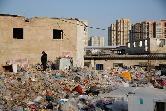A man stands amid trash that covers the debris of demolished houses in Beijing's Baiqiangzi village, which is mainly inhabited by migrant workers, China, December 13, 2017. Photo by Thomas Peter