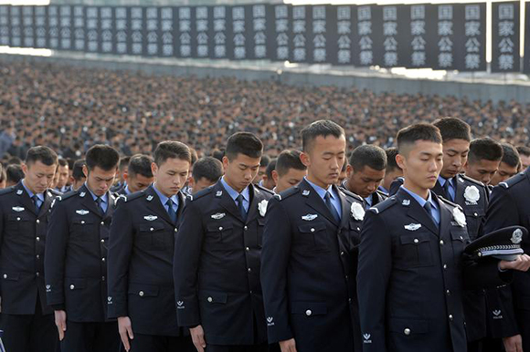 Police pay a silent tribute during a memorial ceremony to mark the 80th anniversary of the 1937 Nanjing Massacre, on the national memorial day in Nanjing, Jiangsu province December 13, 2017. Photo by Stringer