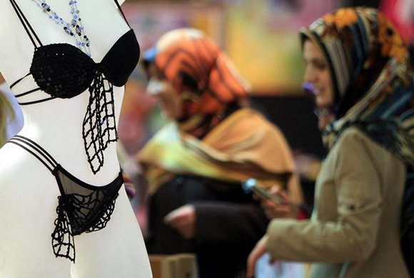 Visitors view a designer's stand next to a mannequin displaying lingerie in a fair as part of Istanbul Fashion Days 2006 in Istanbul Photo by Fatih Saribas