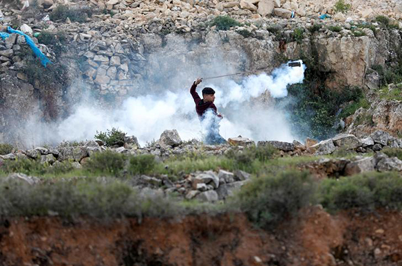 A Palestinian demonstrator returns a tear gas canister fired by Israeli troops during clashes at a protest against Trump's decision on Jerusalem, near Ramallah, in the occupied West Bank March 16, 2018. Photo by Mohamad Torokman